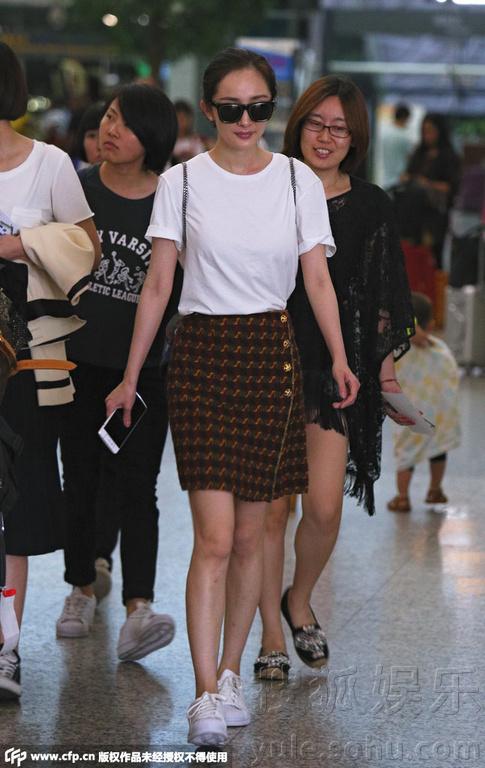 辣妈杨幂身穿白色简约T恤搭小短裙少女范儿十足,当天随意挽起长