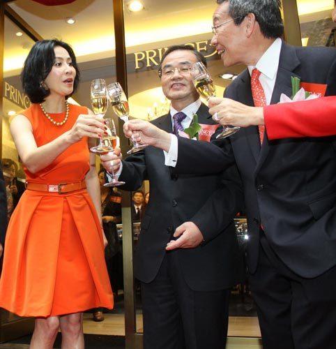 2011年 与珠宝店老板碰杯寒暄. 2011年11月,一身橘红色小礼服现身