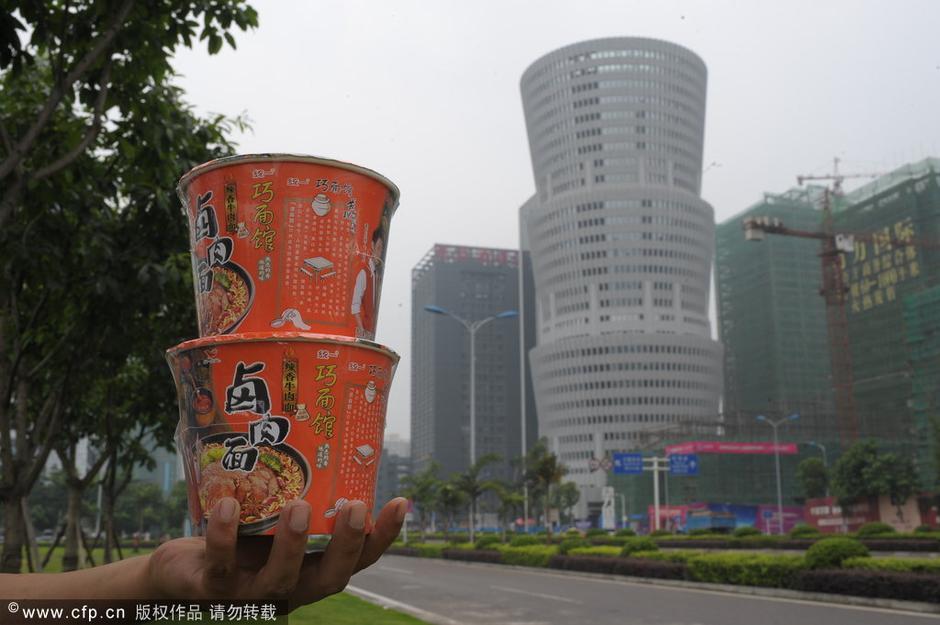 一市民手拿两桶桶装方便面与大楼造型进行对比
