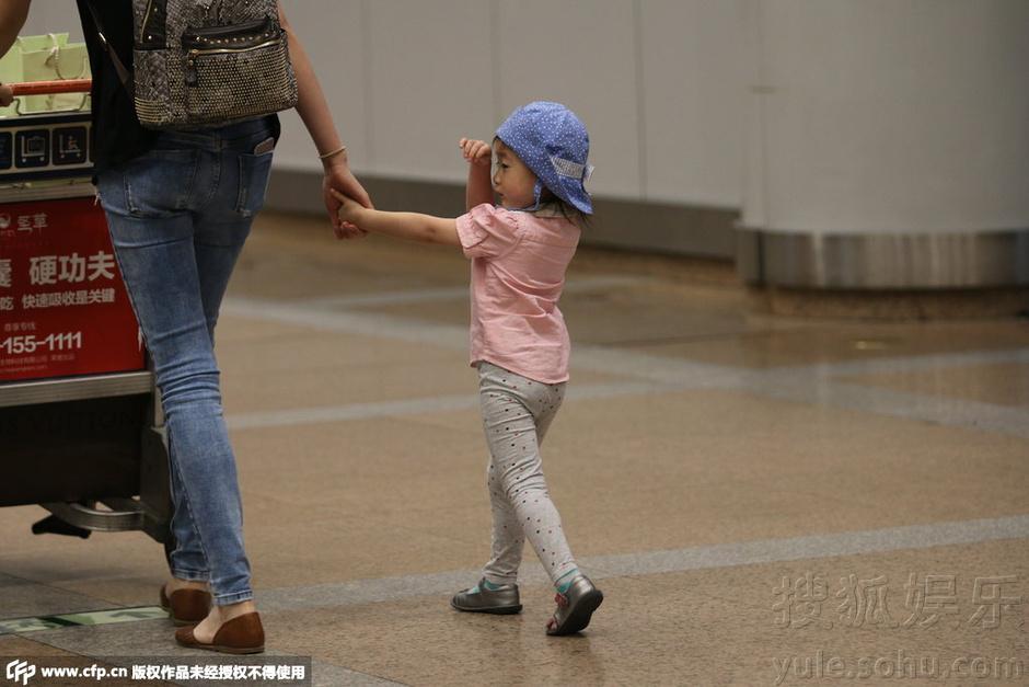 奥莉戴花帽变潮宝可爱 机场获妈妈单臂抱怀乖巧